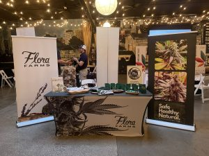 Flora Farms table displayed with merch at MoCannTrade meetup