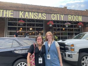 Marketing team poses in front of the Kansas City Room venue